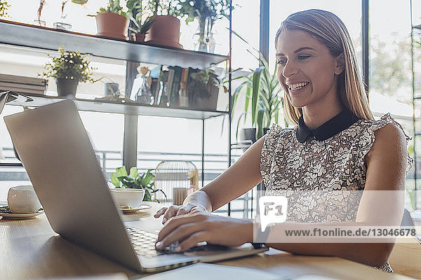 Happy businesswoman using laptop computer while sitting at table in home office