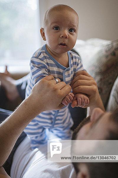 Nahaufnahme eines Vaters  der mit seinem Sohn spielt  während er sich zu Hause auf dem Sofa entspannt