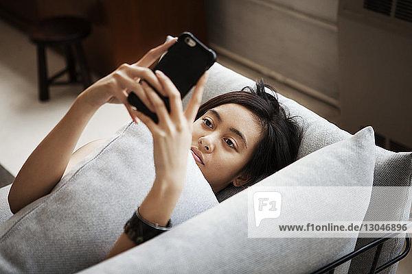 Hochwinkelansicht einer jungen Frau  die ein Smartphone benutzt  während sie zu Hause auf dem Sofa liegt