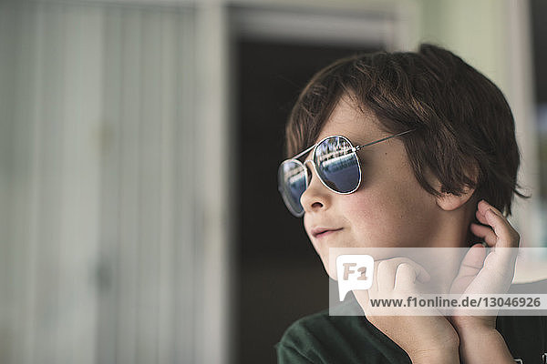 Close-up of boy wearing sunglasses standing against wall at home