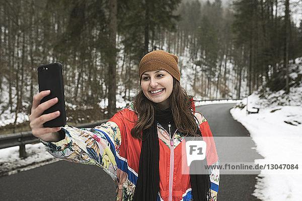 Lächelnde junge Frau  die sich mit einem Smartphone selbstständig macht  während sie im Winter auf einer Landstraße im Wald steht