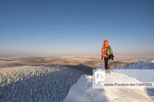 Rückansicht eines Mannes  der auf einem schneebedeckten Berg vor klarem Himmel steht