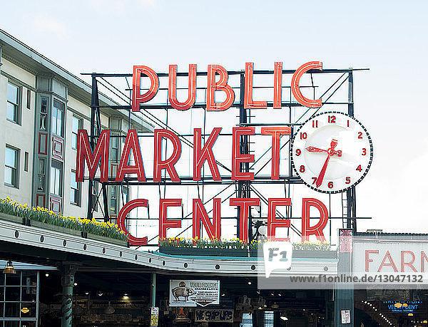 Schild am Dach des öffentlichen Marktzentrums gegen den Himmel