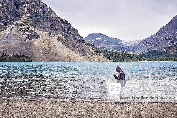Seitenansicht einer Frau mit Kapuzenhemd  die eine Tasse hält  während sie am Seeufer gegen den Himmel steht