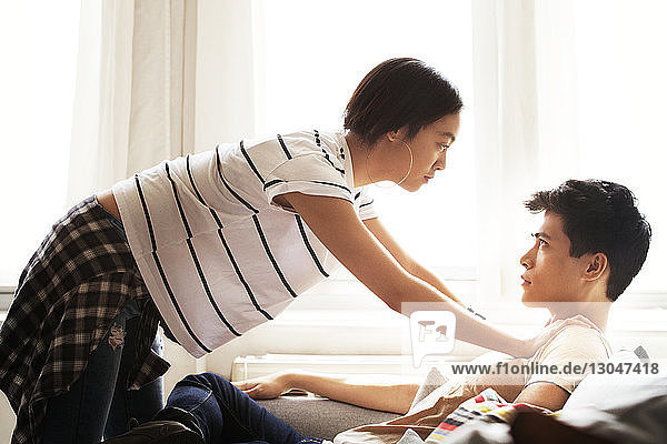 Side view of romantic woman leaning on man sitting at home