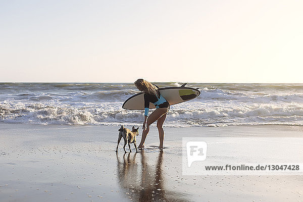 Full length of woman carrying surfboard while standing with dog at beach
