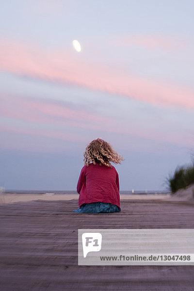 Rückansicht eines Mädchens  das bei Sonnenuntergang am Strand gegen den Himmel sitzt