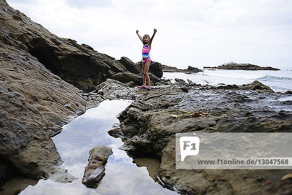 Portrait of girl with hands raised standing on rocks at Laguna Beach