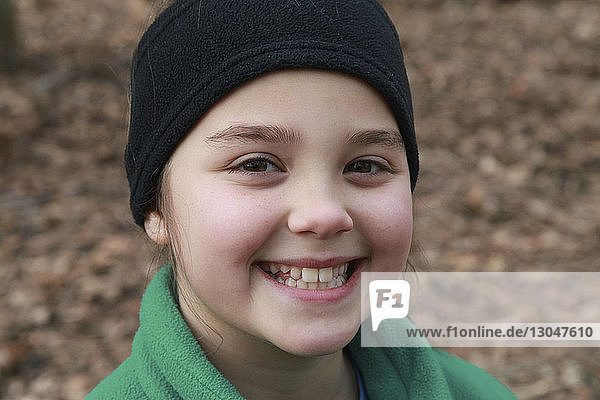 Close-up portrait of smiling girl wearing headband while standing outdoors