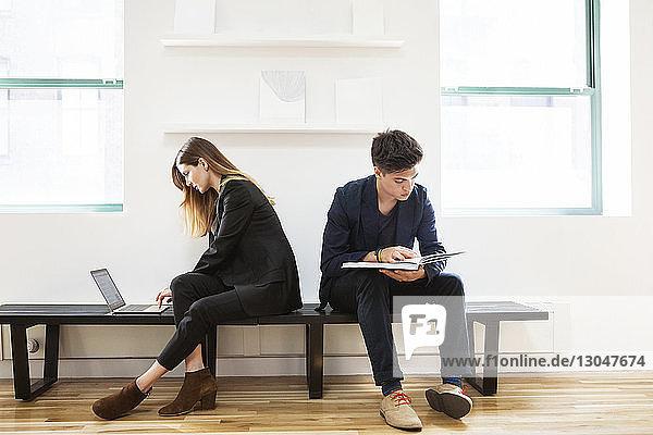 Geschäftsfrau benutzt Laptop  während sie mit einem männlichen Kollegen im Büro sitzt und ein Buch liest Geschäftsfrau benutzt Laptop, während sie mit einem männlichen Kollegen im Büro sitzt und ein Buch liest