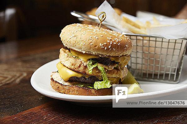 Nahaufnahme eines Cheeseburgers  der in einem Teller auf dem Tisch serviert wird