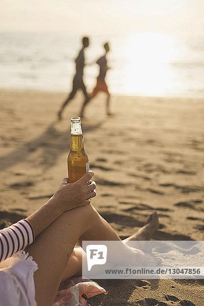 Niedriger Teil einer Frau  die während des Sonnenuntergangs am Strand eine Bierflasche hält