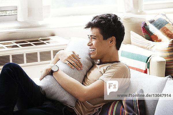 Glücklicher Mann hält Kissen  während er zu Hause auf dem Sofa sitzt