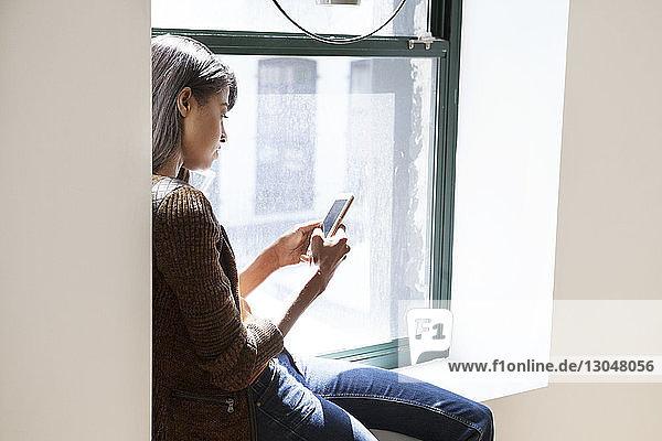 Seitenansicht einer Geschäftsfrau  die ein Smartphone benutzt  während sie im Büro auf dem Fensterbrett sitzt
