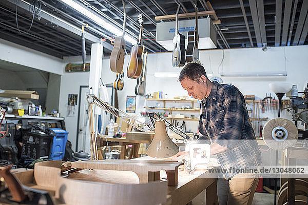 Arbeiter beim Gitarrenbau  während er in der Werkstatt an der Werkbank steht