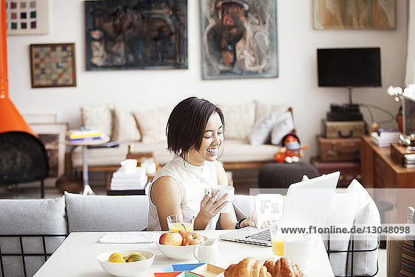 Happy woman holding coffee cup while using laptop
