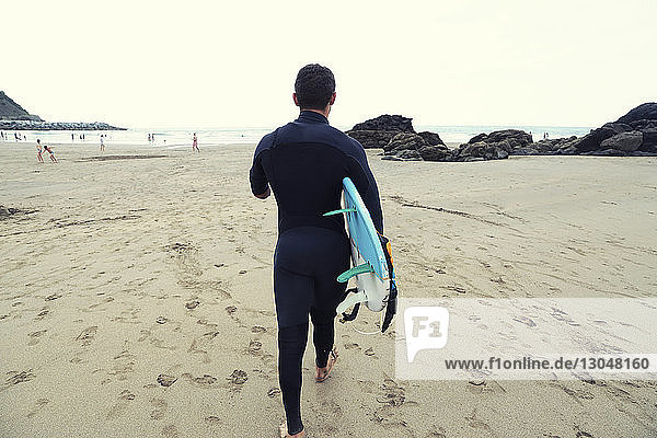 Rear view of man in wetsuit carrying surfboard while walking on beach