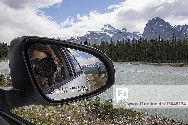Reflection of man photographing with camera seen in side-view mirror of car against mountains