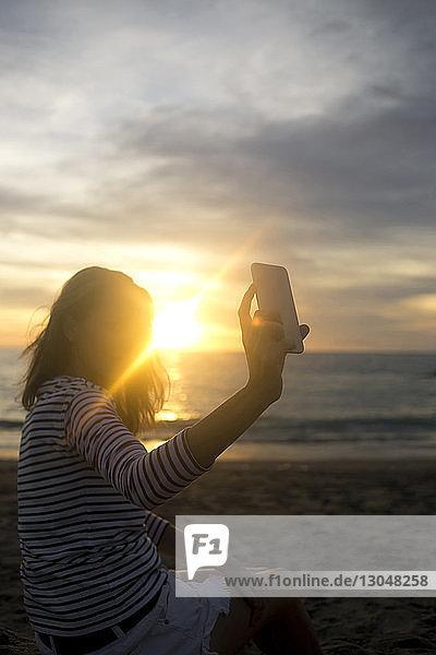 Frau  die bei Sonnenuntergang am Strand gegen den Himmel sitzt