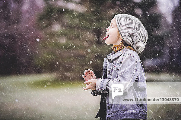 Side view of girl sticking out tongue while standing at park during snowfall