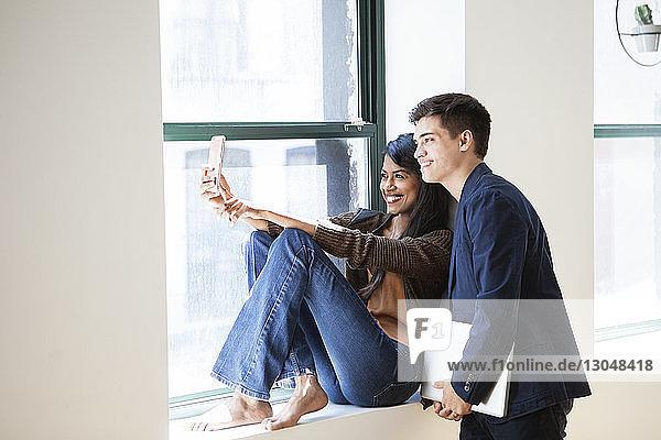Fröhliche Geschäftskollegen  die sich im Kreativbüro am Fenster durch ein Smartphone selbstständig machen