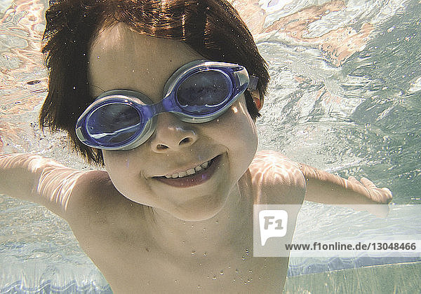 Portrait of shirtless smiling boy swimming underwater in swimming pool