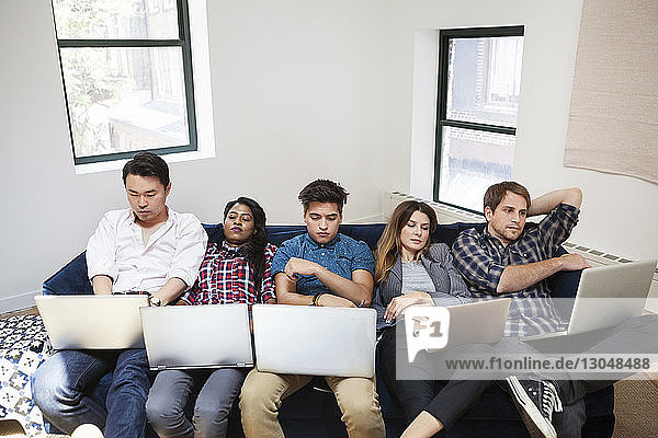 Tired business people using laptop while reclining on sofa in office