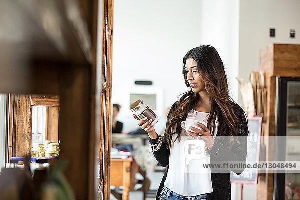 Frau liest Etikett auf Glas  während sie in Cafeteria Kaffeetasse hält