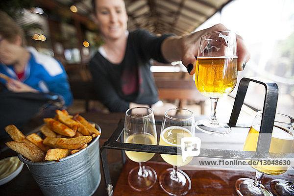 Frau holt Bier vom Regal im Restaurant