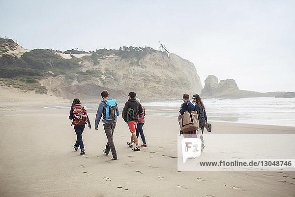 Freunde  die im Urlaub am Strand auf Sand laufen