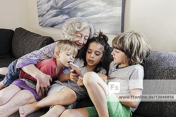 Großmutter und Enkel schauen auf das Smartphone  während sie auf dem Sofa im Wohnzimmer sitzen