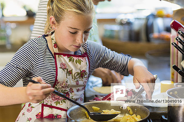 Girl cooking potatoes while standing with mother in kitchen