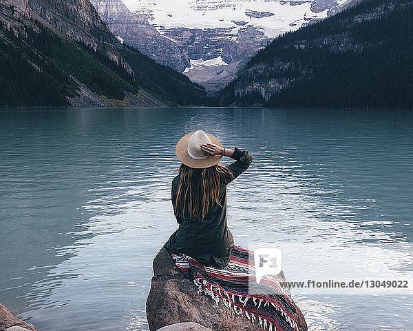 Rückansicht einer Frau mit Sonnenhut  die auf einem Felsen sitzt und auf die Aussicht schaut