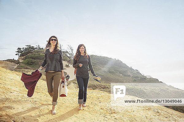 Happy women walking on mountain against sky