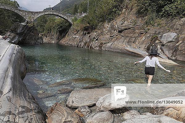 Rückansicht einer Frau beim Spaziergang im Fluss Verzasca bei Ponte dei Salti