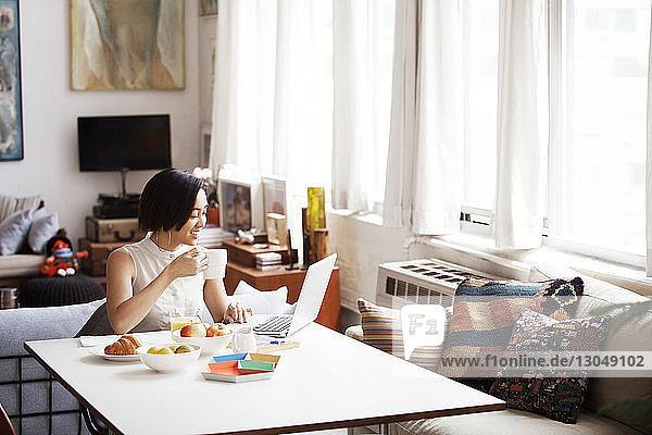 Glückliche Frau hält Kaffeetasse  während sie zu Hause einen Laptop benutzt