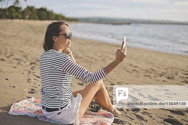 Frau mit Sonnenbrille  die beim Entspannen am Strand Selfie nimmt