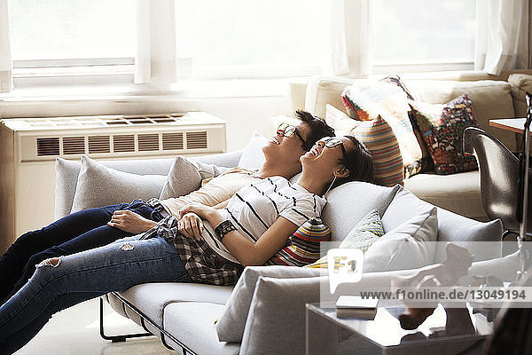 Cheerful multi-ethnic couple reclining on sofa at home