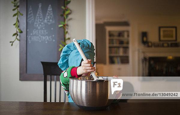 Junge rührt am Tisch mit dem Löffel in einer Schüssel um