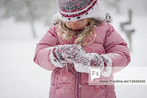 Close-up of cute girl playing with snow