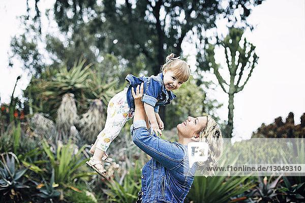 Glückliche Frau hebt Tochter im Hinterhof hoch
