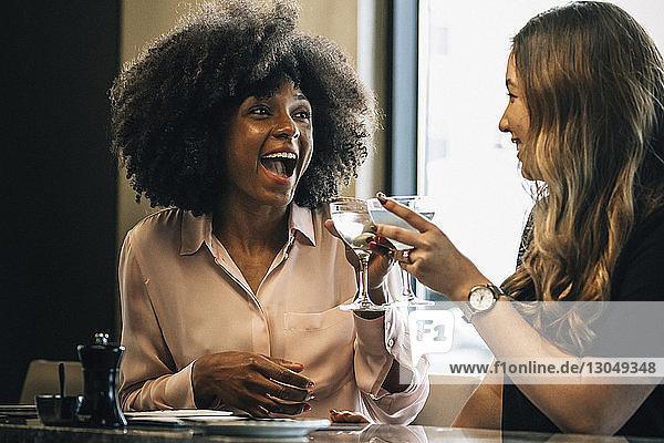 Fröhliche Geschäftsfrauen stoßen im Hotel auf Getränke an