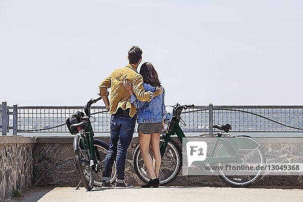 Rückansicht eines Paares  das mit umgebundenen Armen am Beobachtungspunkt gegen den klaren Himmel steht
