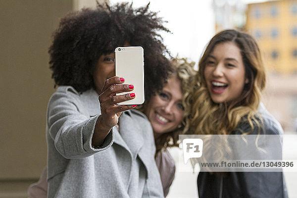 Cheerful businesswomen taking selfie with smart phone