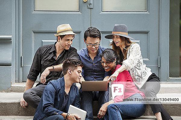 Glückliche Geschäftsleute  die auf Treppen sitzend einen Laptop benutzen