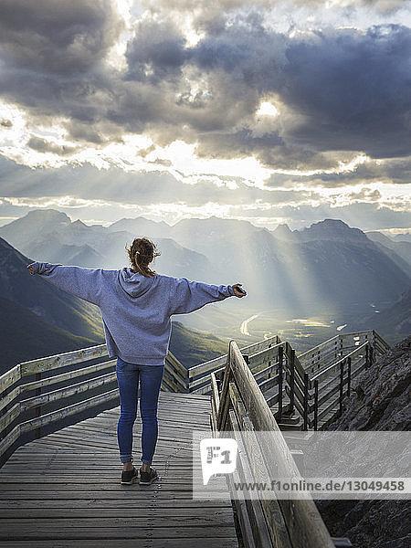 Rückansicht einer Frau mit ausgestreckten Armen  die bei Sonnenaufgang auf Stufen vor bewölktem Himmel steht
