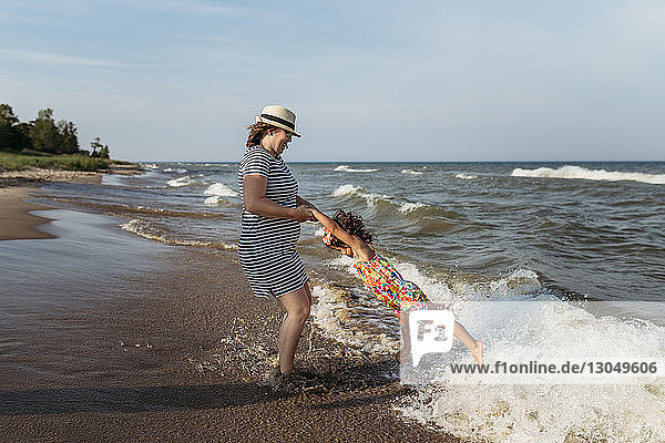 Playful mother spinning daughter at beach against sky
