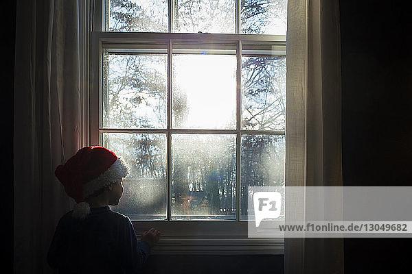 Junge mit Weihnachtsmannmütze schaut durch Fenster  während er zu Hause steht