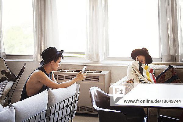 Mann fotografiert in eine Decke gehüllte Frau über einen Tablet-Computer im Wohnzimmer