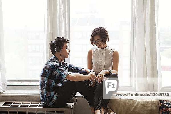 Couple relaxing by window at home